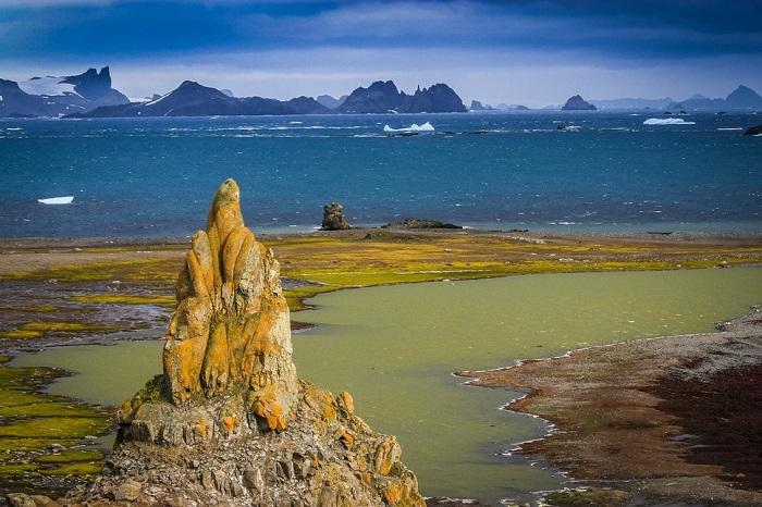 На северном берегу этого острова длиной 1,5 км. находятся, крутые утесы, достигающие в высоту около 70 метров, а южный берег представляет собой пологий склон.