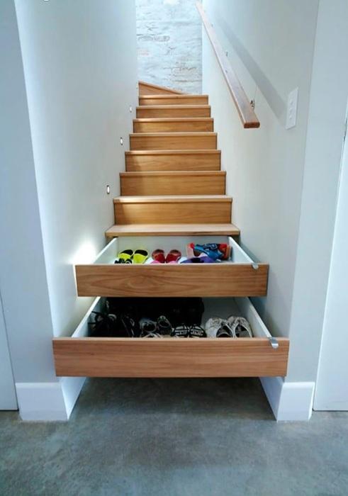 Выдвижные ящики для обуви и других мелких предметов, вмонтированные под лестничными ступеньками.
