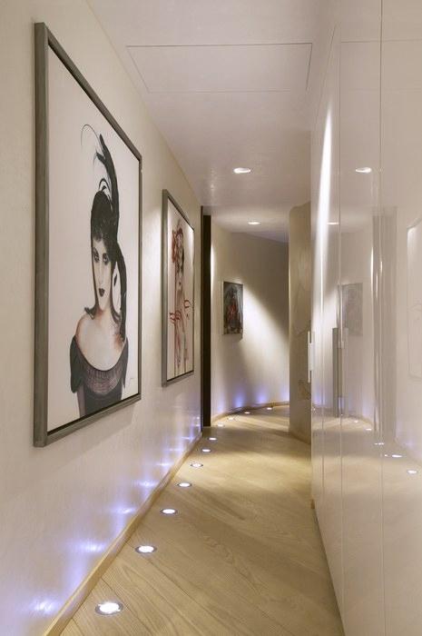 <p>Автор проекта:  Архитектурное бюро B|S. Фотограф: Дмитрий Лившиц.</p> <p>Узкий коридор вполне под стать и минимализму. Белые стены, нижняя точечная подсветка и современное искусство наглядно это доказывают. Глянцевые поверхности стен отражаются друг в друге и делают узкий, кривой коридор очень эффектным и даже объемным.</p>