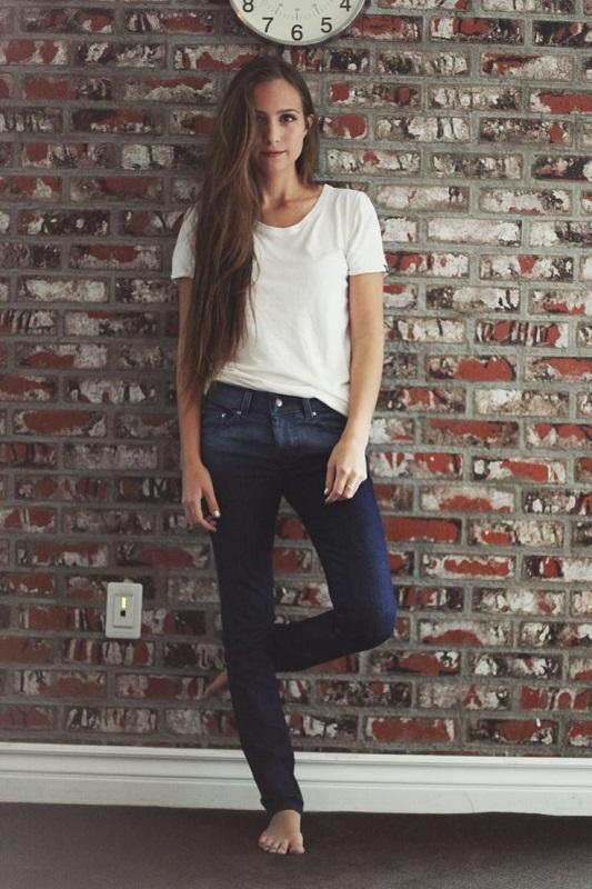 Девушка в темных джинсах и белой футболке