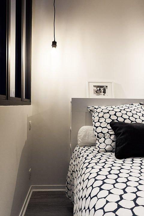Спальня выполнена в сдержанных черно-белых тонах. Если присмотреться, то над изголовьем кровати можно заметить полку, а также полочки сбоку изголовья.
