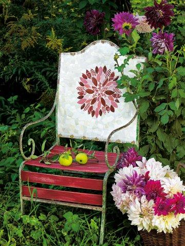 Шезлонге, чья спина украшена мозаикой из кусков плит, которые образуют розовые георгины