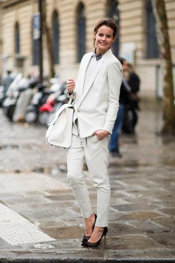 Девушка в белом, брючном костюме на высоких шпильках