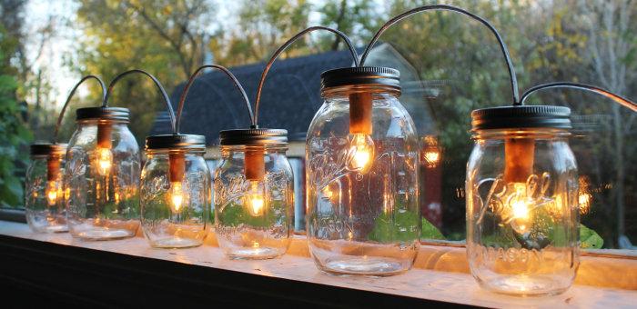 Несколько отрезков кабеля соединяют светильники из стеклянных банок один за другим.