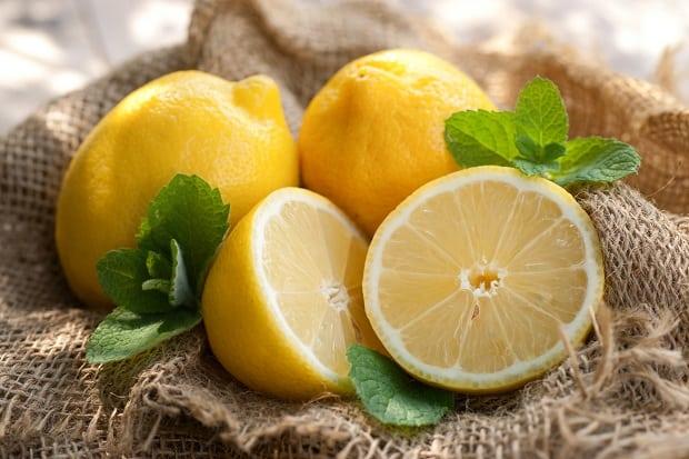 целые лимоны и половинки с зелеными листиками