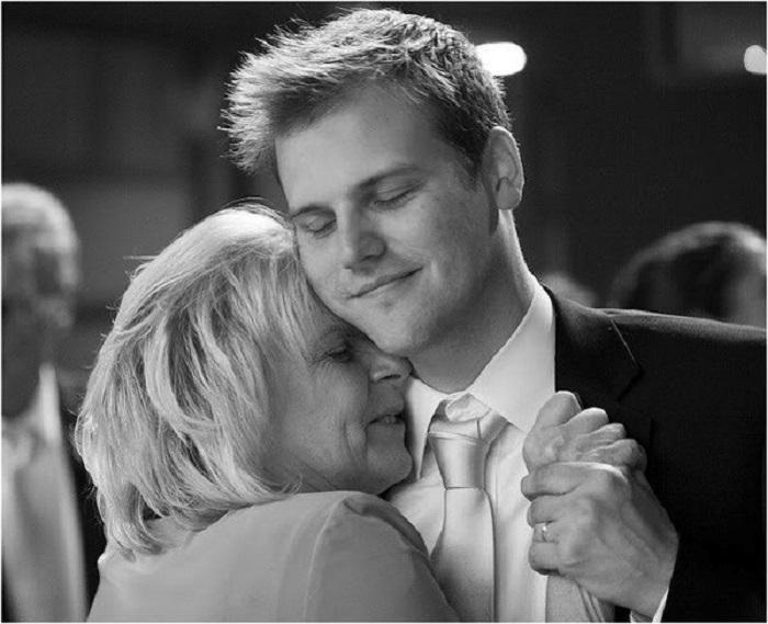 Сын танцует со своей мамой вальс, нежно держа ее руку в своей. | Фото: stihi.ru.