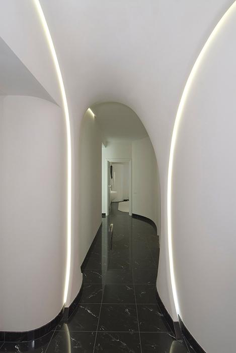 <p>Автор проекта: Наталья Фарносова.</p> <p>Узкие, психоделические коридоры были популярны в девяностые. Головокружительный успех, в прямом и переносном смысле, этих пространств, подчеркивают элипсообразные стены ослепительной белизны, черный пол мрамора и эффектная подсветка. </p>