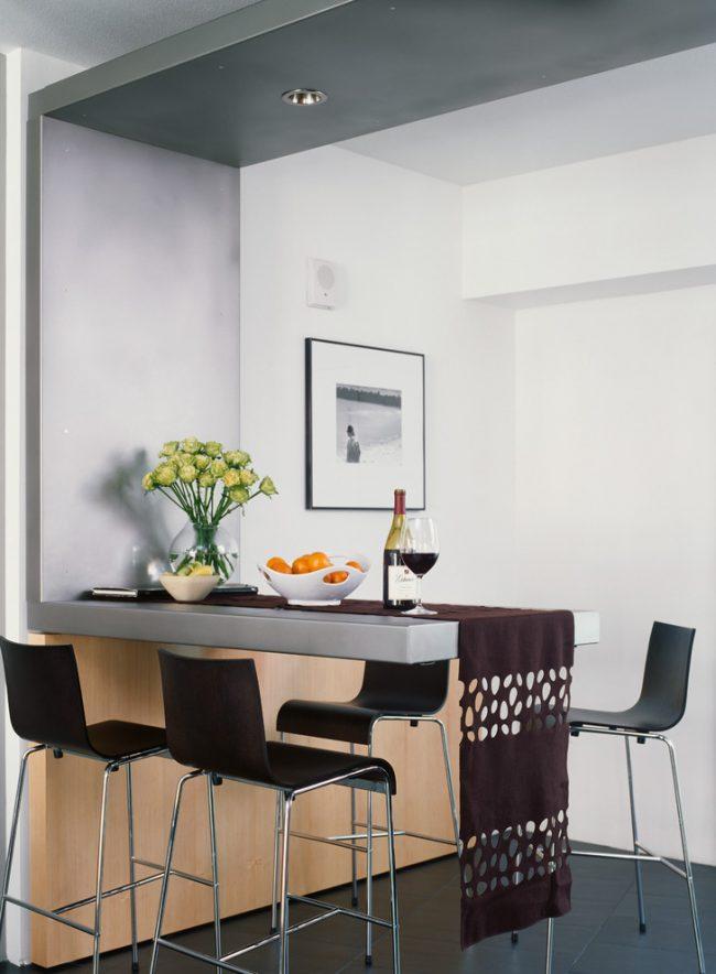 Небольшой обеденный стол, украшенный раннером, в интерьере современной кухни