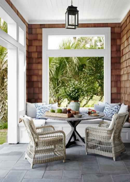 Уютная веранда с диванчиком и плетеными креслами.