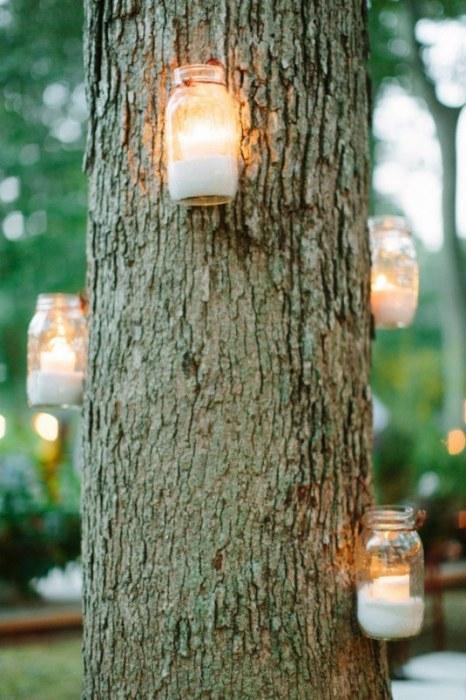 Оригинальные подсвечники из банок можно легко закрепить на любой поверхности, например, на одном из деревьев на территории загородного участка.