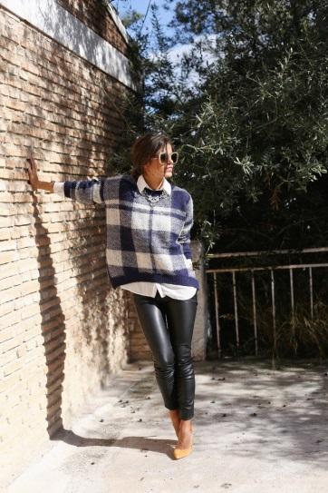 Девушка в кожаных штанах, белой рубашке и свитере в клетку