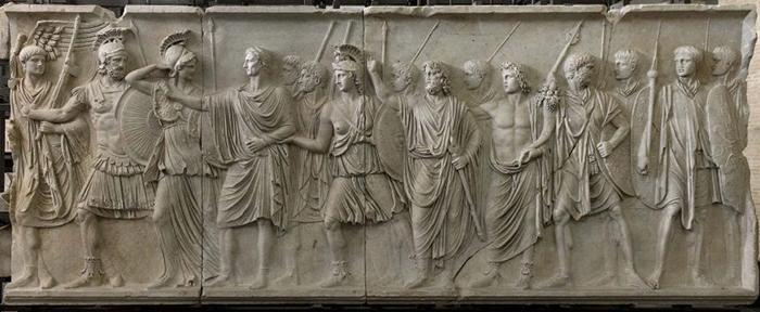 На барельефе когда-то был изображен император Домициан, потом его место занял император Нерва. Изображение преемника (четвертый слева) отличается от остальных фигур неправильным соотношением головы и тела
