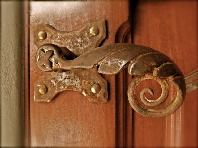Salvaged hardware repurposed on mahogany doors eclectic