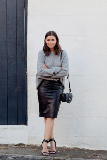 Девушка в кожаной юбке и сером свитере
