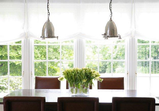 Зеленые цветы на столе хорошо дополняют растительность за окном