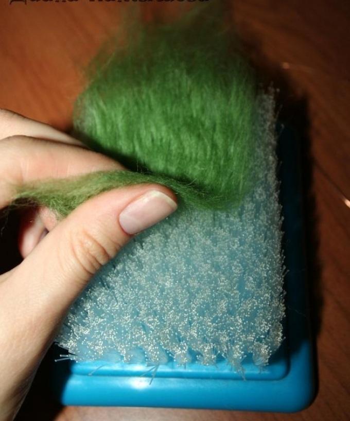 Прядь зелёной шерсти при фелтинге обрабатывается с двух сторон