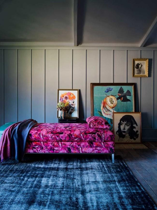Ярко-розовая веллюровая оттоманка создает сказочную атмосферу в затемненной комнате