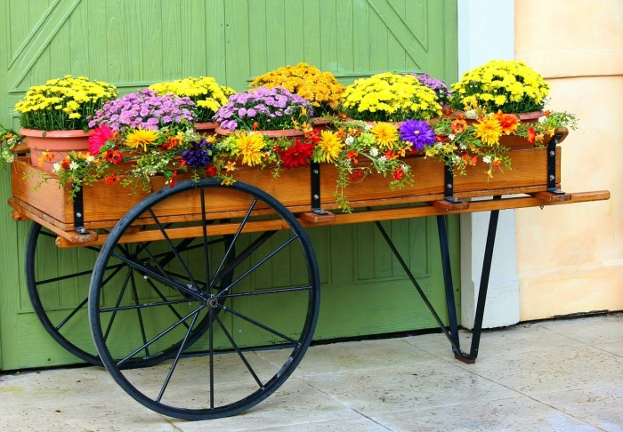 Кованая подставка для цветов в форме двухколёсного грузовой повозки.