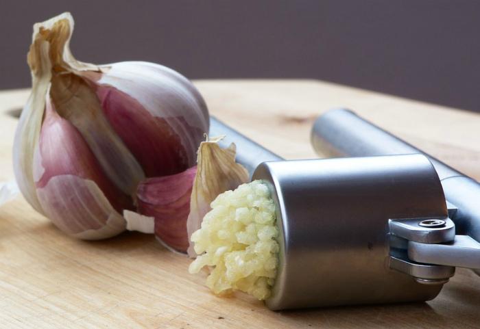 Использование пресса для чеснока. | Фото: Википедия.