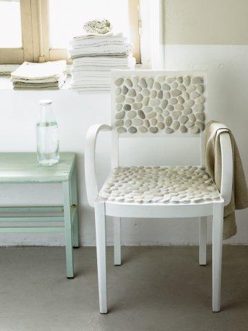 Председатель окрашены в белый цвет и настроить с вкраплениями гальки на земле для сиденья и спинки