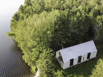 Современный коттедж у озера с воздушными интерьерами в Канаде
