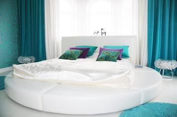 Спальня: огромная круглая кровать в ярком интерьере