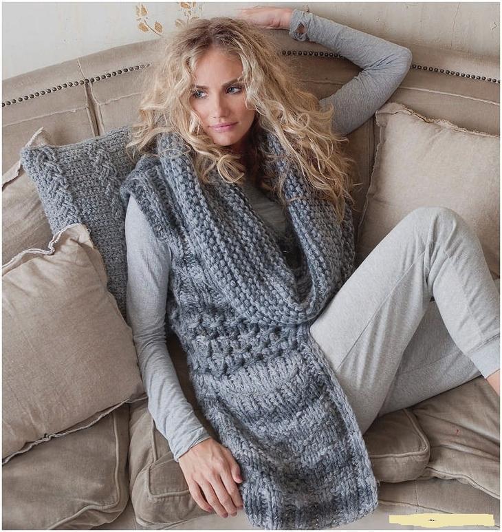 Девушка в длинном вязаном спицами жилете с карманами сидит на диване