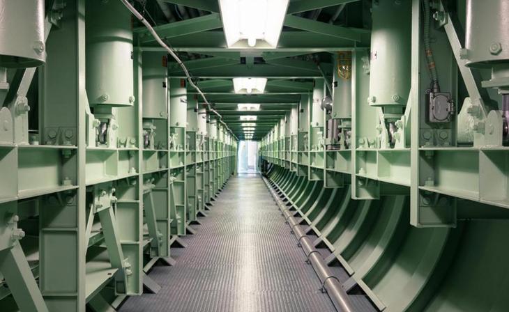 Туннели На самом деле, база не имеет возможности противостоять прямому ядерному удару. Укрепленный бункер способен лишь смягчить последствия упавшей поблизости боеголовки. Сообщающиеся туннели выстланы металлическими фермами, опутанными рядами толстых кабелей. Все вместе несколько напоминает внутренности подводной лодки. Главный переход ведет к центру управления пуском — круглую комнату со стойками оборудования, компьютерными терминалами, рядами циферблатов и переключателей. В середине расположена контрольная консоль, приветствующая оператора рядом огней.
