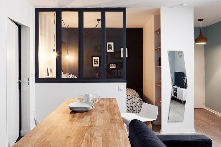 Стеклянная перегородка между гостиной и спальней позволяет улучшить инсоляцию последней. Ведь спальня не имеет собственных окон.